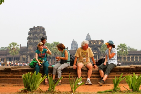 indo china: SIEMREAP, KHMER REPUBLIC - FEBRUARY 24 : Unidentified tourists are relax sitting down in front of classical Khmer construction on February 24, 2013 at Angkor Wat, Siemreap, Khmer Republic.