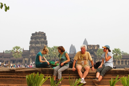 handscraft: SIEMREAP, KHMER REPUBLIC - FEBRUARY 24 : Unidentified tourists are relax sitting down in front of classical Khmer construction on February 24, 2013 at Angkor Wat, Siemreap, Khmer Republic.