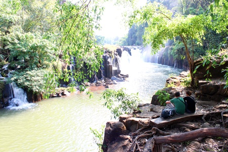 indo china: PAK SE, CHAMPASAK, LAO P.D.R. - JANUARY 13 : Unidentified tourists are relax sitting at Pha Suam Waterfall on January 13, 2013 at Pak Se, Champasak, Lao P.D.R.