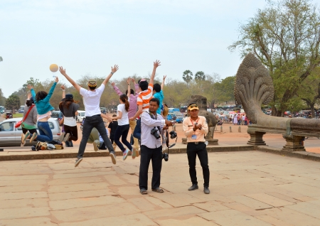 handscraft: SIEMREAP, KHMER REPUBLIC - FEBRUARY 24 : Unidentified tourists are jumping at entrance of classical Khmer construction on February 24, 2013 at Angkor Wat, Siemreap, Khmer Republic.