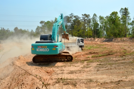 MUANG, MAHASARAKHAM - APRIL 5 : Unidentified workers are working with excavator and truck in land remodeling area on April 5, 2013 at Ban Tha Ngam, Huay Aang, Muang, Mahasarakham, Thailand.
