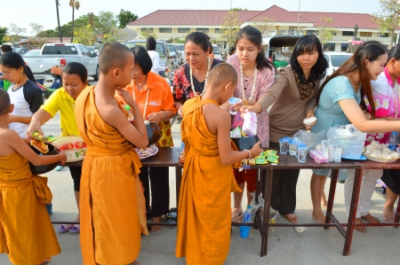 kinfolk: PAYAKKAPHUMPHISAI, MAHASARAKHAM - APRIL 13 : Unidentified people are giving food offering to Buddhist novices in Thai New Year or Songkran Festival on April 13, 2013 at City Hall Plaza, Payakkaphumphisai, Mahasarakham, Thailand. Editorial