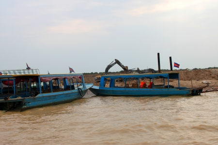 SIEMREAP, KHMER REPUBLIC - FEBRUARY 23 : Excavators are digging bank of the greatest freshwater lake in the world on February 23, 2013 at Tonle Sap Lake, Siemreap, Khmer Republic. Stock Photo - 19033101
