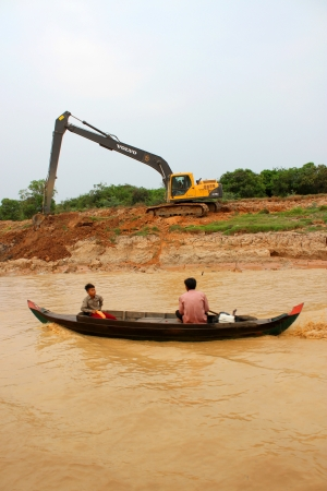 SIEMREAP, KHMER REPUBLIC - FEBRUARY 23 : Excavator is digging bank of the greatest freshwater lake in the world on February 23, 2013 at Tonle Sap Lake, Siemreap, Khmer Republic. Stock Photo - 19033162