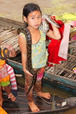 SIEMREAP, KHMER REPUBLIC - FEBRUARY 23 : Unidentified Khmer girl and snake round her neck is in beggar way of life in the greatest freshwater lake in the world on February 23, 2013 at Tonle Sap Lake, Siemreap, Khmer Republic. Stock Photo - 19033306
