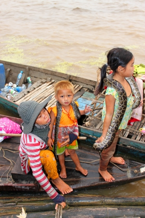 SIEMREAP, KHMER REPUBLIC - FEBRUARY 23 : Unidentified Khmer woman and children are on their beggars way of life in the greatest freshwater lake in the world on February 23, 2013 at Tonle Sap Lake, Siemreap, Khmer Republic. Stock Photo - 19033309