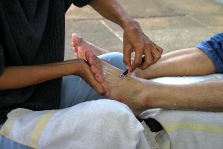 human feet massage on footpath in rural village of Thailand photo