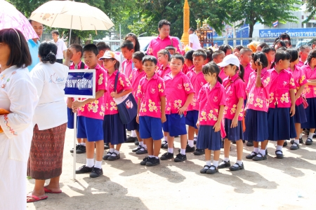 participate: MAHASARAKHAM, THAILAND - JULY 19 : Unidentified people and pupils aged 7 - 10 years are participating in Buddhist Lent festival parade at city hall plaza on July 19, 2013 in Mahasarakham, Thailand.
