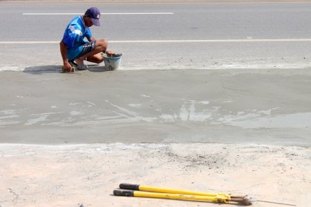 MAHASARAKHAM, THAILAND - JULY 13 : Unidentified man is spreading concrete floor and working hard at Mahasarakham - Roi Et road on July 13, 2013 in Mahasarakham, Thailand.