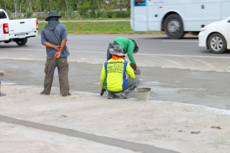 MAHASARAKHAM, THAILAND - JULY 13 : Unidentified men are spreading concrete floor and working hard at Mahasarakham - Roi Et road on July 13, 2013 in Mahasarakham, Thailand.