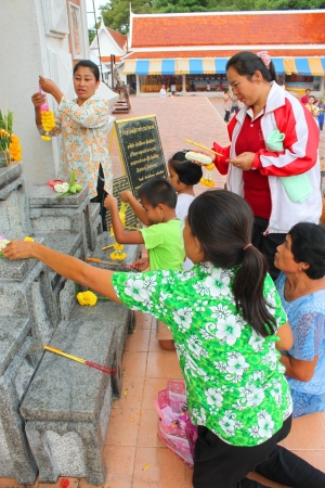 7 9 years: MAHASARAKHAM, THAILAND - JULY 22 : Unidentified children aged 7 - 9 years and people worship Buddha statue at Nadun Pagoda in Buddhist Lent festival on July 22, 2013 in Mahasarakham, Thailand.