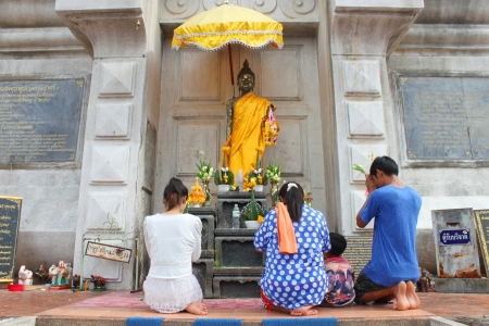 MAHASARAKHAM, THAILAND - JULY 22 : Unidentified child aged 4 years and people worship Buddha statue at Nadun Pagoda in Buddhist Lent festival on July 22, 2013 in Mahasarakham, Thailand.