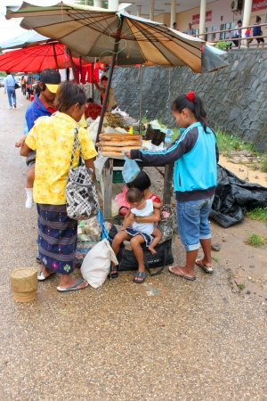 VANG TAO, LAO P D R  - JULY 28   Unidentified tourists with children aged 3 - 6 years are shopping at Thai - Lao border business center on July 28, 2013 in Vang Tao, Lao P D R