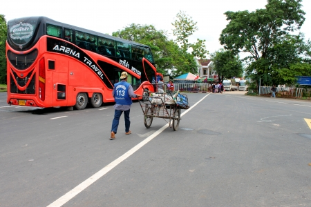 VANG TAO, LAO P D R  - JULY 28   Unidentified  man is pushing empty cart forward to Thai - Lao border on July 28, 2013 in Vang Tao, Lao P D R