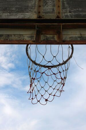 the height of a rim: Old basketball net and board on blue sky background Stock Photo