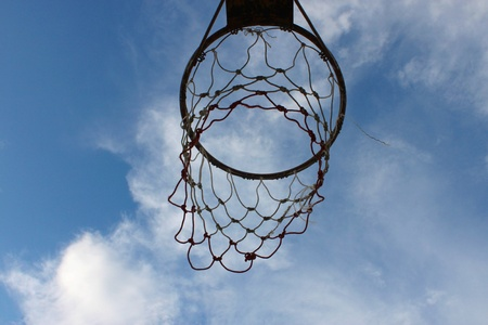 the height of a rim: Old basketball net on blue sky background Stock Photo