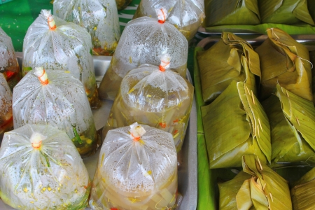 steamed fish with curry paste in banana leaves and take away food in market photo