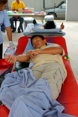 MAHASARAKHAM, THAILAND - AUGUST 21   Unidentified man is laying in bed for blood donation at Padung Nari school on August 21, 2013 in Mahasarakham, Thailand