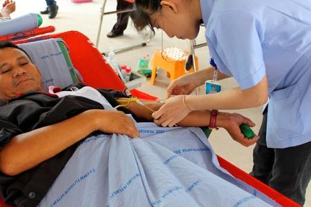 MAHASARAKHAM, THAILAND - AUGUST 21   Unidentified nurse is stabbing needle in man