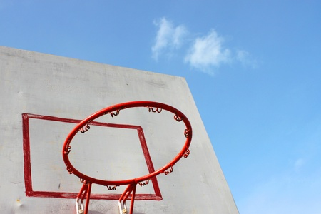 the height of a rim: Old basketball hoop and board on blue sky background Stock Photo