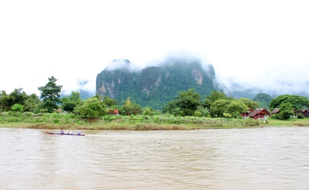 long tailed boat: VANG VIENG, LAO P D R  - AUGUST 24   Unidentified tourists are traveling on long-tailed boat trip in Song River on August 24, 2013 in Vang Vieng, Lao P D R