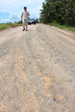 geodesist: MAHASARAKHAM, THAILAND - SEPTEMBER 16   Unidentified man surveys local road for public  construction on September 16, 2013 in Mahasarakham, Thailand  Editorial