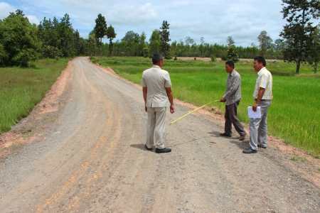 geodesist: MAHASARAKHAM, THAILAND - SEPTEMBER 16   Unidentified men survey local road for public  construction on September 16, 2013 in Mahasarakham, Thailand
