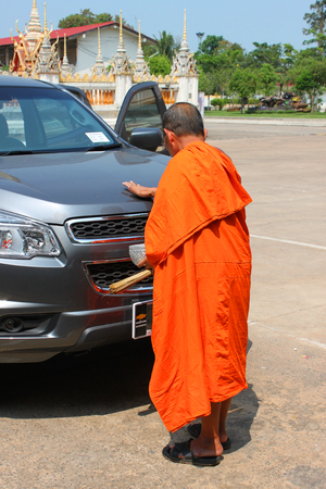 anoint: ROI-ET, THAILAND - OCTOBER 13   Unidentified monk prays and sprinkle holy water after anoints holy powder in a new car at wat Burapa Piram on October 13, 2013 in Roi-Et, Thailand
