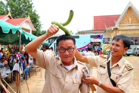 snake head: MAHASARAKHAM, THAILAND - AUGUST 22   Unidentified man is put long snake gourd on head as a snake head old man in public healthy mobile project at kerng village on August 22, 2013 in Muang Mahasarakham, Thailand