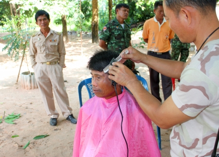 MAHASARAKHAM - OCTOBER 17   Unidentified man is getting a haircut by hairdresser in public healthy mobile project at Non Mi village on October 17, 2013 in Mahasarakham, Thailand