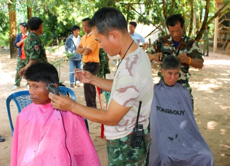 MAHASARAKHAM - OCTOBER 17   Unidentified men are getting a haircut by hairdressers in public healthy mobile project at Non Mi village on October 17, 2013 in Mahasarakham, Thailand