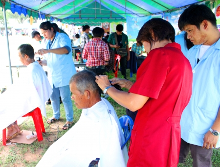 MAHASARAKHAM - SEPTEMBER 24   Unidentified men are getting a haircut by hairdressers in public healthy mobile services at Nong Ku village on September 24, 2013 in Muang Mahasarakham, Thailand