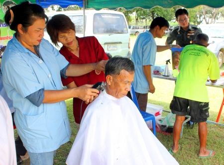MAHASARAKHAM - SEPTEMBER 24   Unidentified man is getting a haircut by hairdresser in public healthy mobile services at Nong Ku village on September 24, 2013 in Muang Mahasarakham, Thailand
