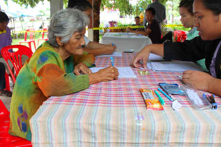 official ballot: MAHASARAKHAM - SEPTEMBER 14   Unidentified old woman goes to vote for village headman election at Tha Rae Pattana on September 14, 2013 in Muang, Mahasarakham, Thailand