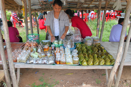 MAHASARAKHAM - AUGUST 6   Unidentified man hawker is preparing take away foods for sell at Tha Rae Wattana village market stall on August 6, 2013 in Mahasarakham, Thailand  Stock Photo - 23003372