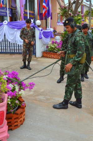 metal detector: MAHASARAKHAM - DECEMBER 17   Soldiers use metal detector for searching explosive bomb before grand opening of public library on December 17, 2013 in Mahasarakham, Thailand  Editorial