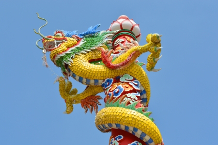 Chinese style dragon statue on post at entrance of shrine in Thailand photo