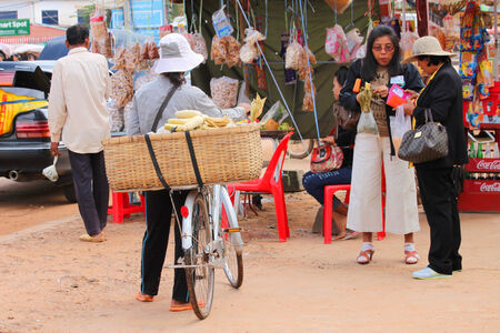 ka: KA LAN, CAMBODIA - NOVEMBER 23   Unidentified Khmer woman is selling boiled corn on bicycle at local market on November 23, 2013 in Ka Lan, Cambodia