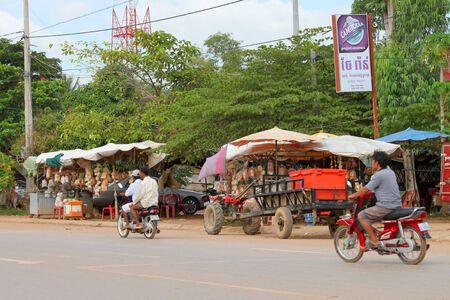 KA LAN, CAMBODIA - NOVEMBER 23   Transportation by motorcycle is popular and comfortable on the local road on November 23, 2013 in Ka Lan, Cambodia
