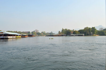 boater: KANCHANABURI, THAILAND - JANUARY 22   Tourists travel on a raft boat and have dinner at the river Kwai on January 22, 2014 in Kanchanaburi, Thailand  There are also many tours visiting the famous bridge