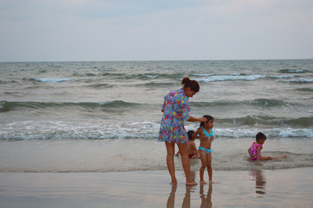 THA MAI, CHANTABURI - FEBRUARY 26   Woman and children aged 5 years play at Chao Lao Beach on February 26, 2014 in Tha Mai, Chantaburi, Thailand