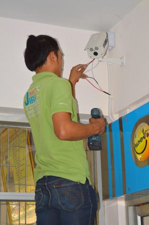 MUANG, MAHASARAKHAM, THAILAND - MARCH 7   Technician man setup cctv camera on district hall wall on March 7, 2014 in Mahasarakham, Thailand