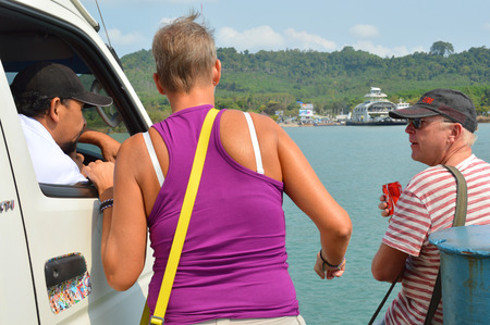 KOH CHANG, TRAT - FEBRUARY 28   Tourists are talking with car chauffeur at prow of ferry boat on February 28, 2014 in Koh Chang, Trat, Thailand  Koh Chang is the country