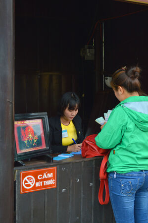 communual: HOI AN, VIET NAM - MARCH 15   Tourist is buying a ticket for shopping at walking street on March 15, 2014 in Hoi An, Viet Nam  Hoi An is world heritage old town with old aged traditionally kept cultural activities, habits and customs