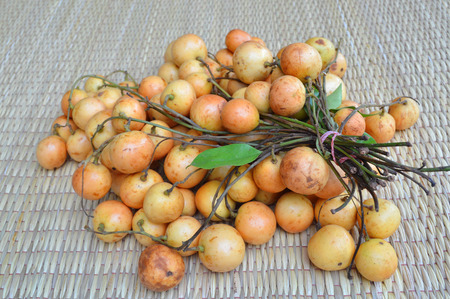 Mafai or Baccaurea ramiflora on woven mat background photo