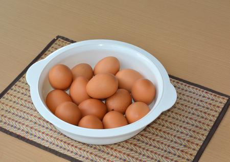 chicken eggs in plastic utensil on table photo