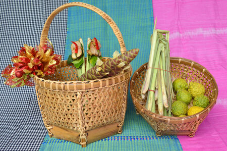 herbs in handmade woven bamboo basket and cotton clothes background photo