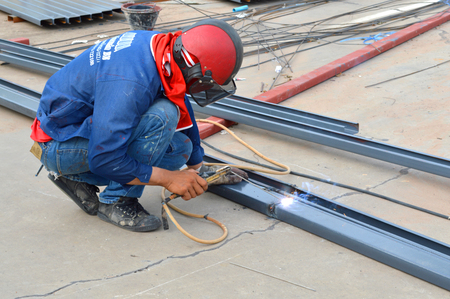 MAHASARAKHAM - JULY 7   Welder is working at car parking of Serm Thai Complex Department store on July 7, 2014 in Mahasarakham, Thailand