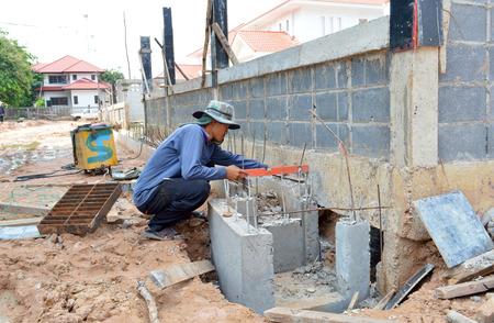 constructs: MAHASARAKHAM, THAILAND - MAY 29   Masonry worker constructs sanitary sewer of judge residence house on May 29, 2014 in Mahasarakham, Thailand