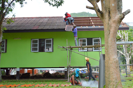 klong: KHAO YAI, KORAT - JUNE 21 : Workers are repairing house roof of Klong Sai Resort on June 21, 2014 in Khao Yai, Korat, Thailand.